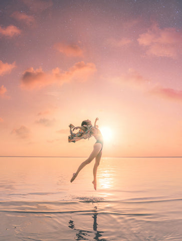 Woman jumping over ocean with stars and sunset in the background