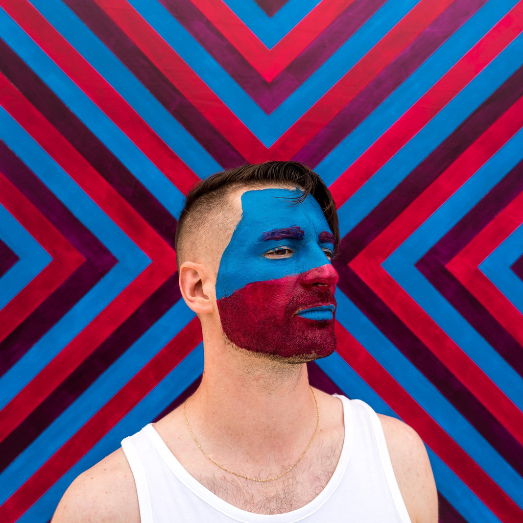 There There with blue and magenta face paint, staring into the distance, against a vibrant, striped background