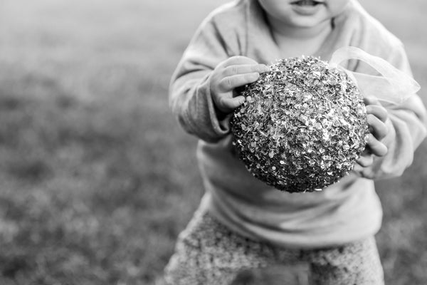 Little girl holding large bauble for Essex Mama photographed by Chelmsford Photographer Kika Mitchell Photography for Christmas