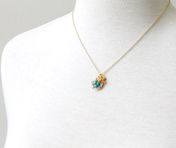 Gold bird charm and nest with turquoise eggs necklace