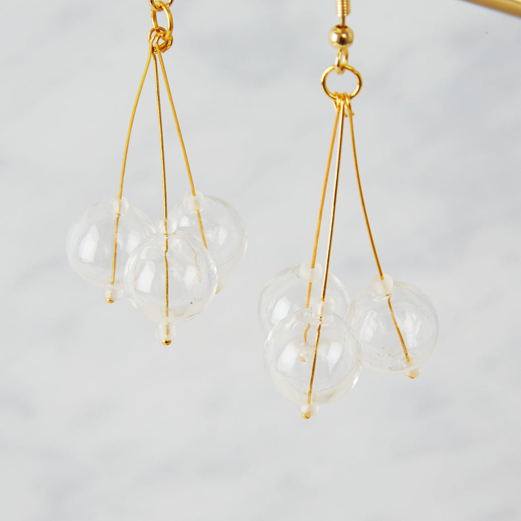 brass earrings with three glass beads in a pendulum