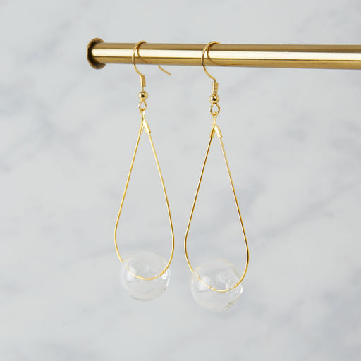 Brass earrings with a single clear glass bead
