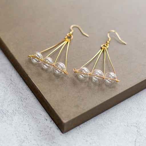 Brass earrings with three clear glass beads in a pyramid shape by  a UK black owned jewlery brand