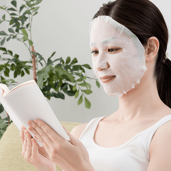 woman wearing sheet mask reading a book