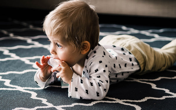 baby lying on rug eating pacifier