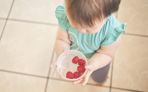 baby girl holding bowl of raspberries