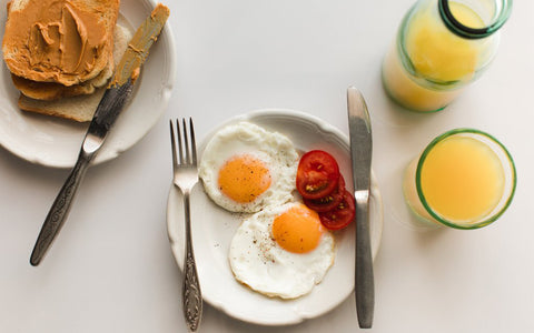 sunny-side up eggs on plate with peanut butter toast and orange juice