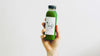 Matcha RTD beverage in plastic bottle held up in front of white background