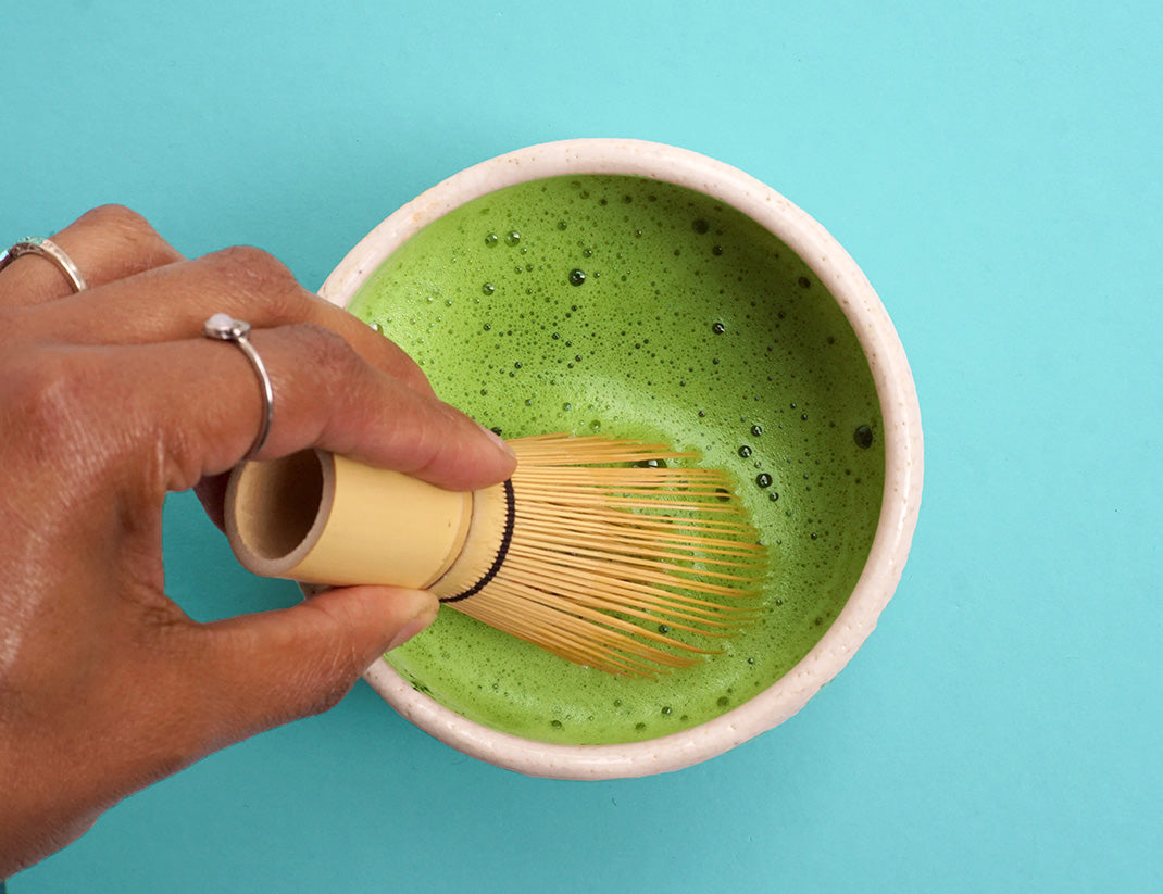 bulk matcha for nutraceutical purposes being whisked in a bowl over a blue table.