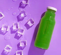 a bottle of matcha green tea on a purple background next to scattered ice cubes