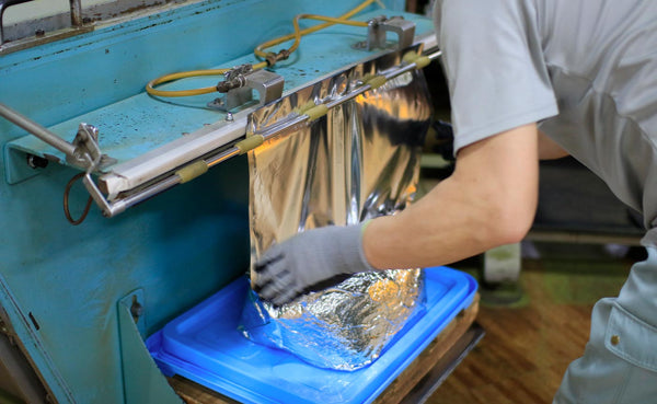 Warehouse worker bundles a package of bulk matcha powder in silver foil wrap.