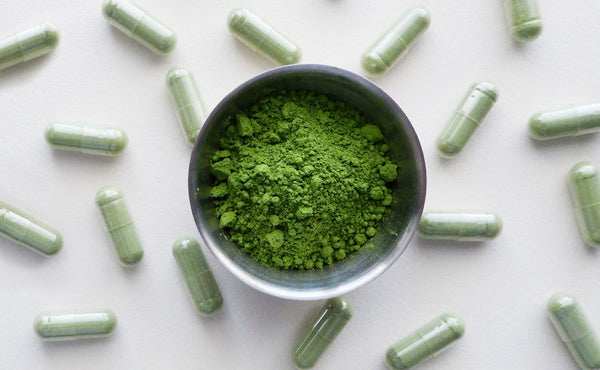 A bowl of matcha tea powder surrounded by small, green matcha supplements.