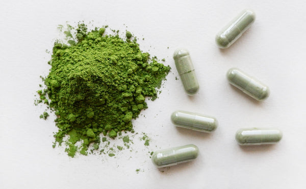 A pile of matcha powder surrounded by green matcha supplement pill capsules.