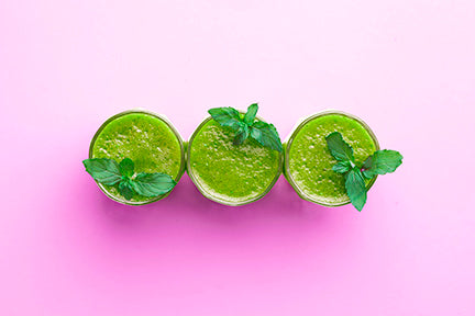 Three glasses of matcha green juice adorned with mint leaves, on a pink background.