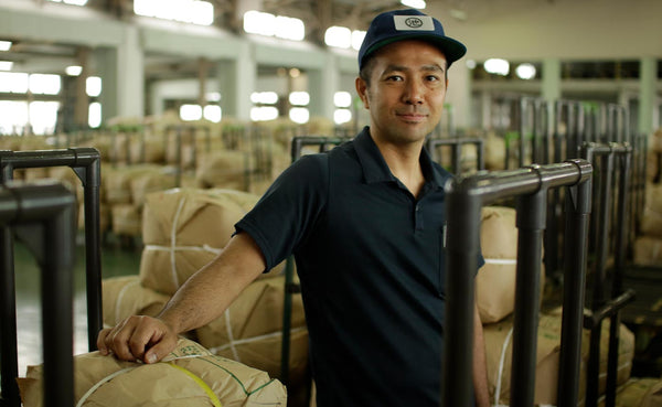 Warehouse worker stands besides tied bundles of bulk matcha powder.