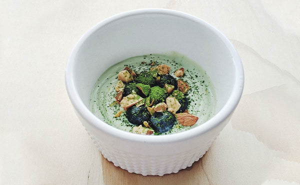 A green smoothie bowl with probiotic matcha green tea sprinkled on top.