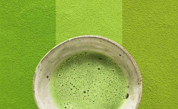 Matcha tea beverage in a stoneware cup against green striped background