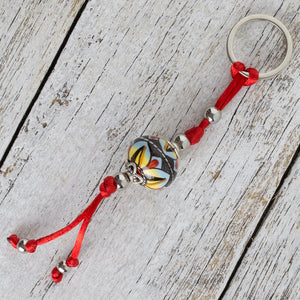 Keyring with hand painted ceramic ball - blue, yellow, red and black