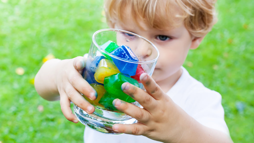 A boy is holding a glass jar of colored icecube