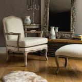 The Rocaille Chair and Footstool in Off-white linen mix in decorated room with mirror and rug