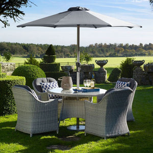 2019 Bramblecrest Monterey 4 Seat Garden Dining Set With 120cm Round Table in a garden with decorative hedges