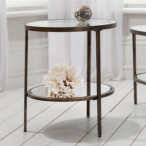 Bronze Side Table in middle of room with flowers and ornaments