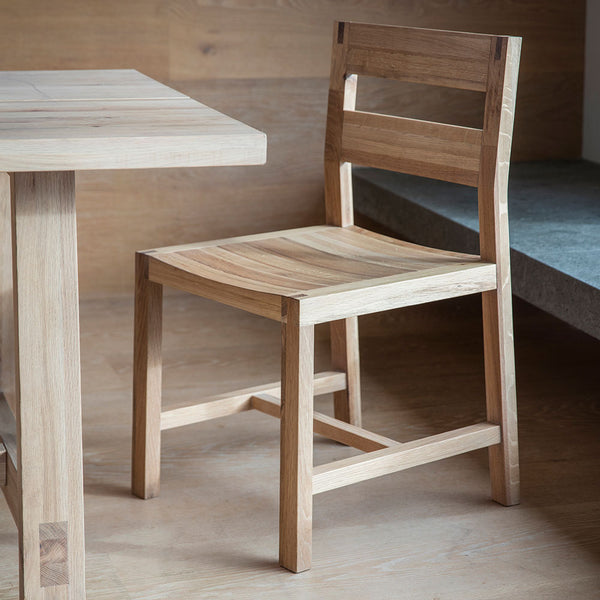 The Serenity Chair at table in situation in wooden room