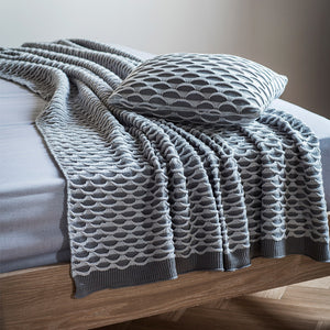 Two grey throw on bed with matching pillow