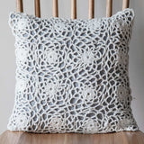 close up of white and grey crochet cushion on wooden chair