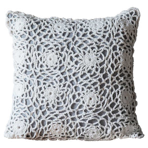 close up of white and grey crochet cushion with white background