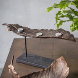 Bronze feather candle holder on table with accessories