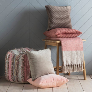 Velvet blush cushion in pile of cushions on a stool, with blankets