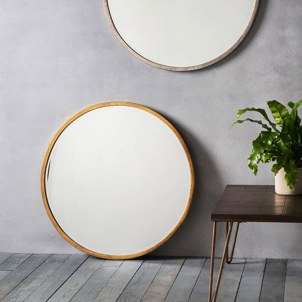 Smith Round Mirror in Gold leaning against a wall