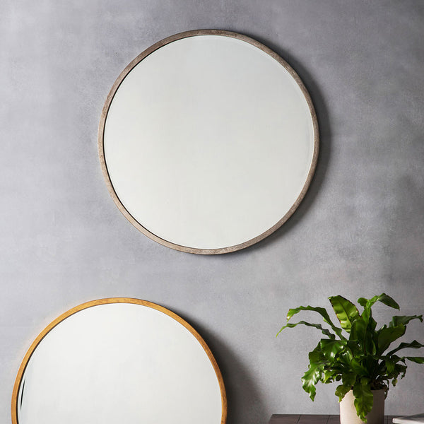 Smith Round Mirror in Silver hanging on a wall