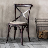 The Cross Dining Chair - Black next to log basket
