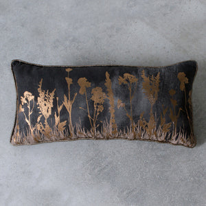 Charcoal and gold floral cushion on grey background