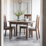 The Rural Round Ext Oak Dining Table in Smokey Oak (1.2m)situated in a room with chairs and a flower centrepiece