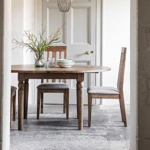 The Rural Round Ext Oak Dining Table in Smokey Oak (1.2m) viewed through a doorway situated in a room with chairs and a flower centrepiece