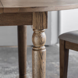 The Rural Round Ext Oak Dining Table in Smokey Oak (1.2m) leg detail with side of chair