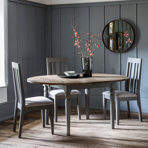The Rural Round Ext Oak Dining Table in Slate Grey (1.2m) situated in room with flowers and mirror