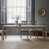 The Rural Extending Oak Dining Table Set in Smokey Oak situated in a dining room with large widows