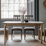 The Rural Extending Oak Dining Table Set in Smokey Oak situated in a dining room with wooden floor and grey decals