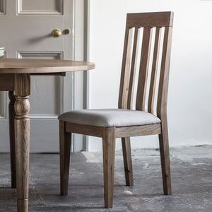 The Rural Dining Chair in Smokey Oak at table in white room with grey floor