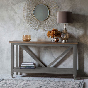 The Rural Trestle Table Slate Grey situated in room with mirror on wall and accessories