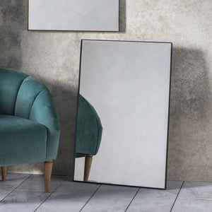 Simple Mirror in Black leaning against a wall