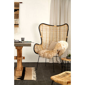 The Nordic Rattan Egg Chair with blanket in room with dark floor