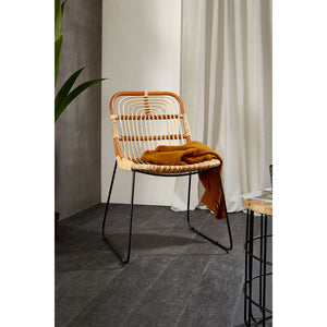 The Nordic Rattan Dining Chair in room with blanket on dark floor