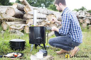 All-in-one cooking station being used by a man camping