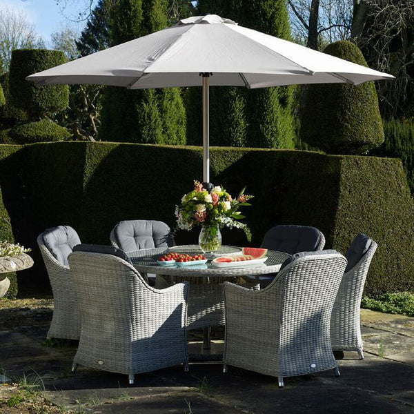 2019 Bramblecrest Monterey 6 Seat Garden Dining Set With 140cm Round Table & Lazy Susan on patio in front of large decorative hedges