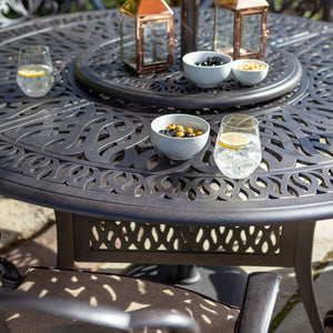 Close up of 2019 Hartman Amalfi 6 Seat Round Dining Table With Snacks, A Glass Of Gin & An Open Parasol